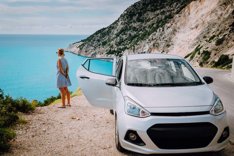 Mujeres cerca del coche alquilado con la puerta abierta que gozan de la playa de Myrtos concepto de la vocaci?n del viaje Kefalon fotos de archivo