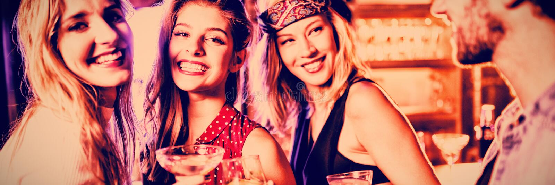Mujeres con el amigo masculino en el contador en club nocturno imagen de archivo