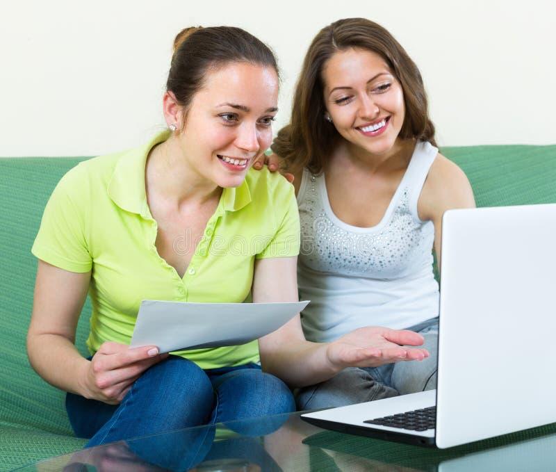 Mujeres con el ordenador portátil en el interior casero imagen de archivo libre de regalías