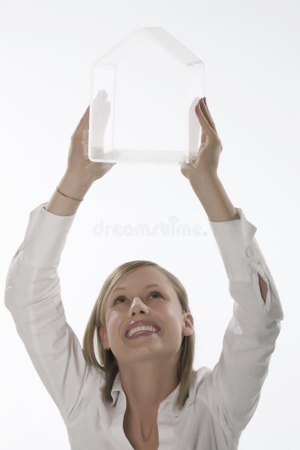 Mujeres con la mano transparente de la pequeña casa imagenes de archivo