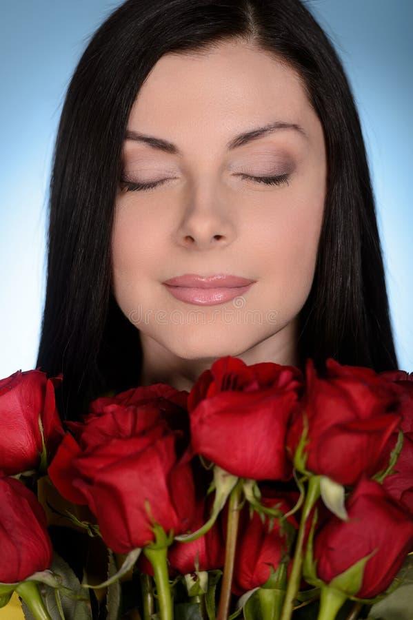 Mujeres con las rosas rojas. Mujeres de mediana edad hermosas que llevan a cabo un bunc foto de archivo libre de regalías