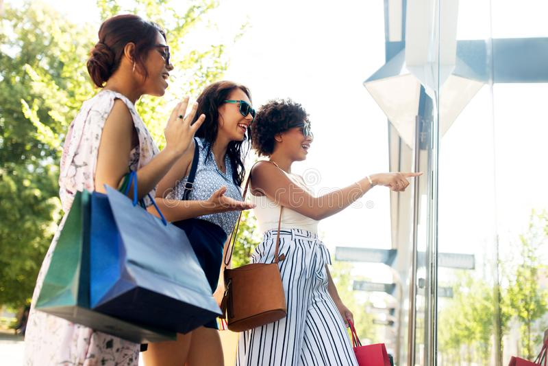 Mujeres con los panieres que miran la ventana de la tienda foto de archivo libre de regalías