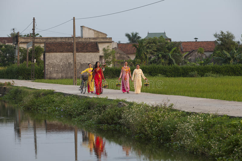 Mujeres de Christian Vietnamese que llevan Ao Dai mientras que camina a la iglesia en una carretera nacional imagenes de archivo