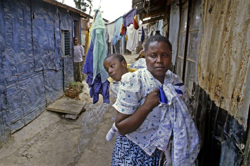 Mujeres de la vida de cada día con el niño minusválido en los tugurios, Nairobi fotografía de archivo libre de regalías