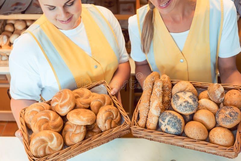 Mujeres de las ventas en la panadería que presenta el pan fresco foto de archivo