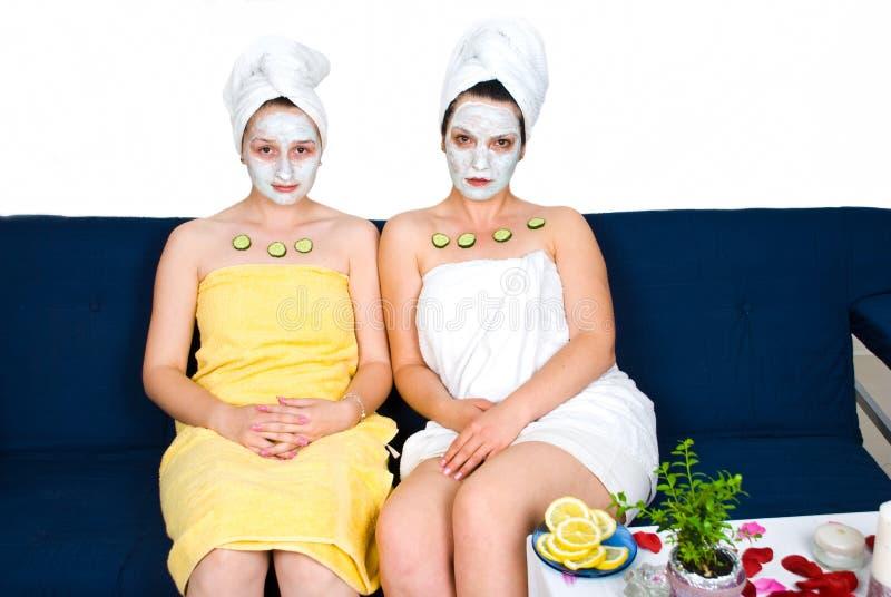 Mujeres de los amigos con la máscara facial en el centro turístico de balneario foto de archivo libre de regalías