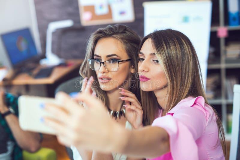 Mujeres de negocios alegres sonrientes que toman un selfie en la oficina imagen de archivo