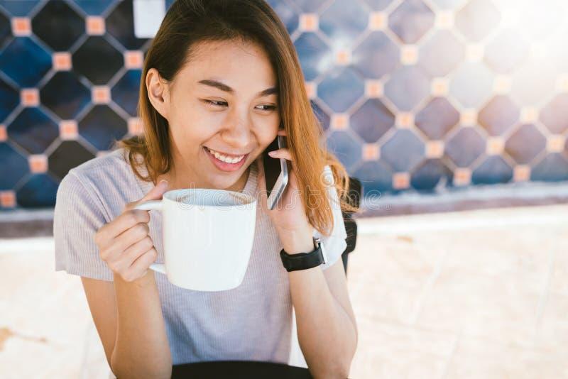 Mujeres de negocios asiáticas de la sonrisa feliz que usan el teléfono celular que habla que se sienta en café y que sostiene una foto de archivo libre de regalías