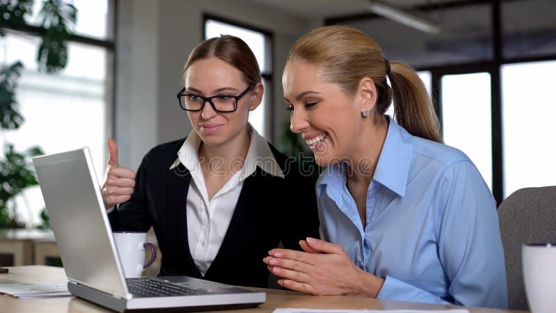 Mujeres de negocios felices que leen las buenas noticias en el ordenador portátil, inversión del dinero que disfruta foto de archivo