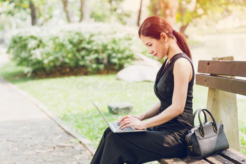 Mujeres de negocios hermosas usando el ordenador portátil en la sentada al aire libre del parque en el banco imagen de archivo