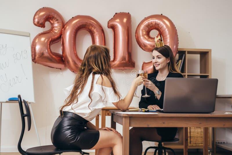 Mujeres de negocios jovenes que celebran la Navidad, nuevo año en el cargo fotos de archivo libres de regalías