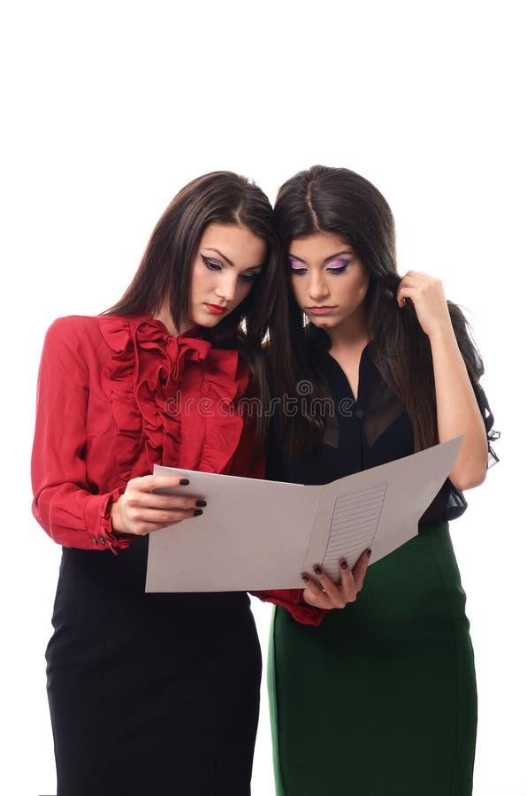 Mujeres de negocios jovenes que hacen un cierto papeleo imagen de archivo libre de regalías