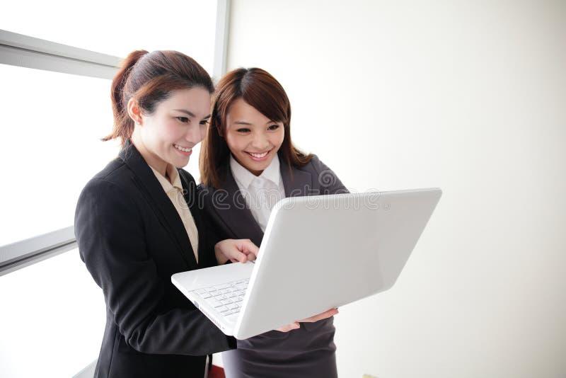 Mujeres de negocios mirada y conversación de la sonrisa fotografía de archivo libre de regalías