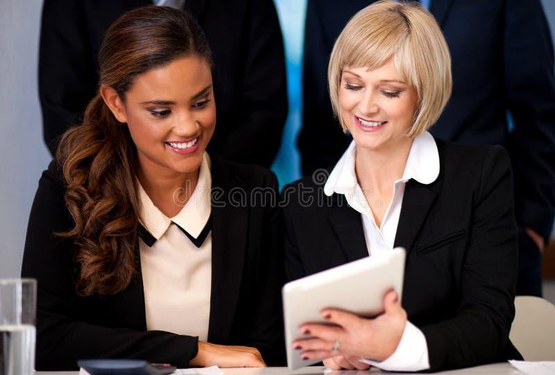 Mujeres de negocios que hojean en el dispositivo de la tableta imágenes de archivo libres de regalías