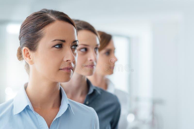Mujeres de negocios que presentan y que miran lejos foto de archivo