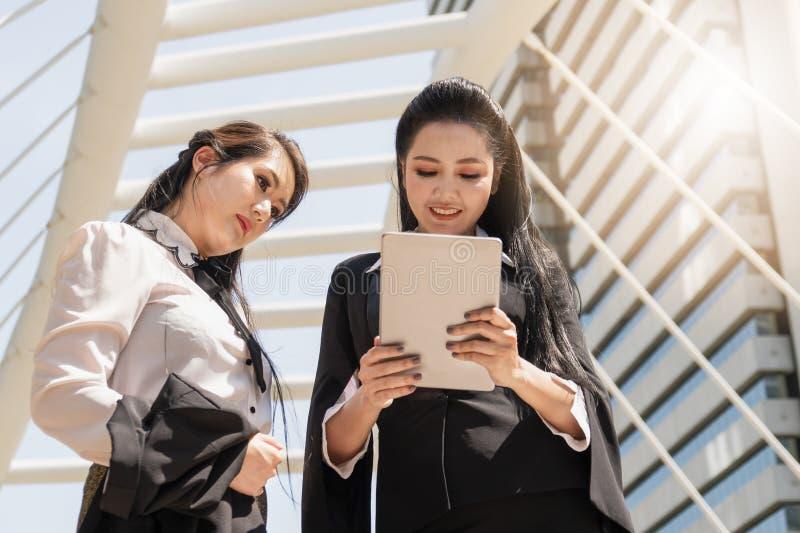 Mujeres de negocios que tienen charla del negocio y que usan la tableta del ordenador al aire libre fotos de archivo