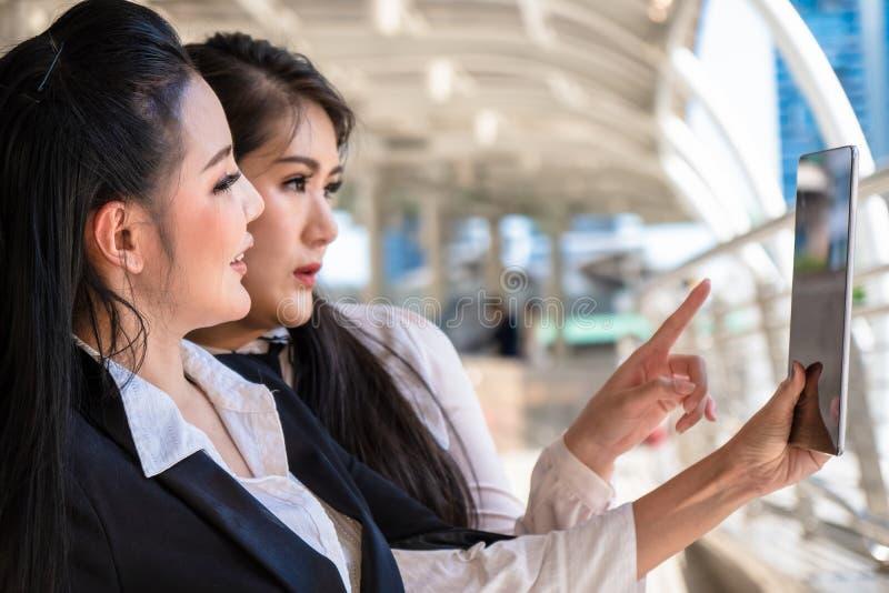 Mujeres de negocios que tienen charla del negocio y que usan la tableta del ordenador al aire libre fotografía de archivo libre de regalías