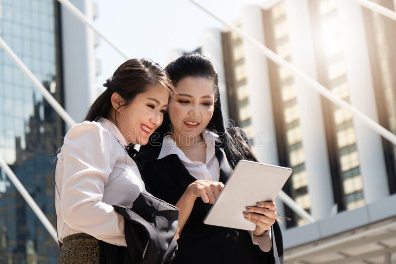 Mujeres de negocios que tienen charla del negocio y que usan la tableta del ordenador al aire libre imagen de archivo libre de regalías