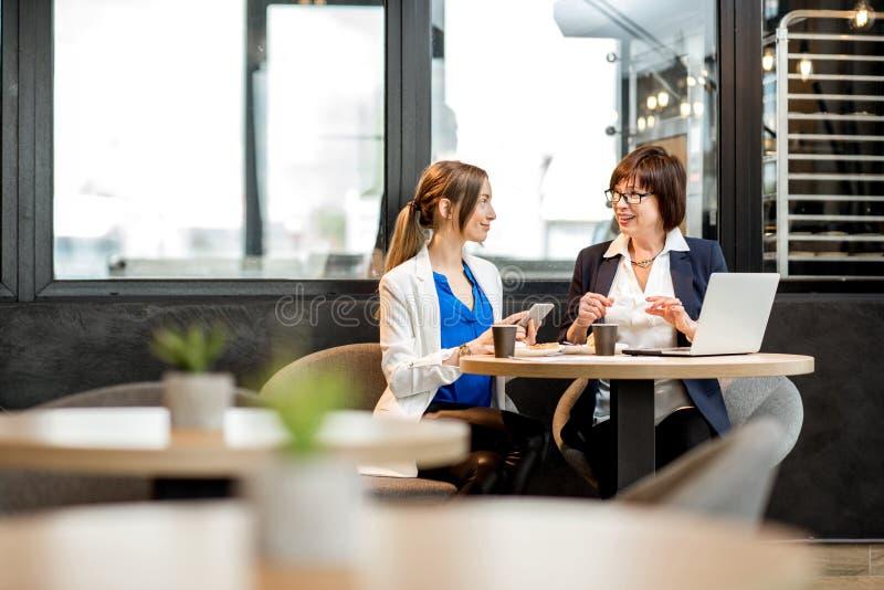 Mujeres de negocios que trabajan en el café fotos de archivo