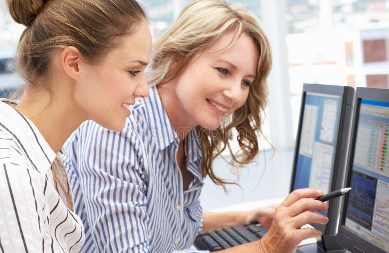 Mujeres de negocios que trabajan junto en los ordenadores foto de archivo