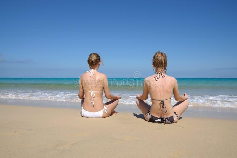 Mujeres de Oung meditating en la playa tropical imagen de archivo libre de regalías