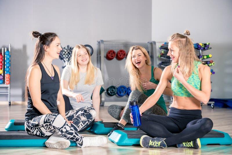 Mujeres de risa felices después de entrenar en hablar del gimnasio fotografía de archivo