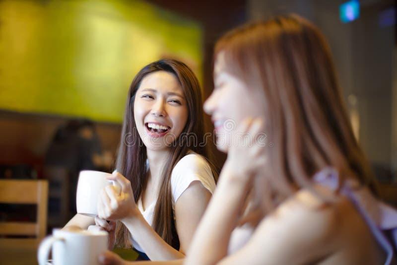 Mujeres de risa jovenes en cafetería foto de archivo