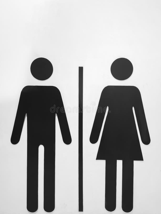 Mujeres de simbolizaci?n y hombres de la muestra negra en una pared blanca imagenes de archivo