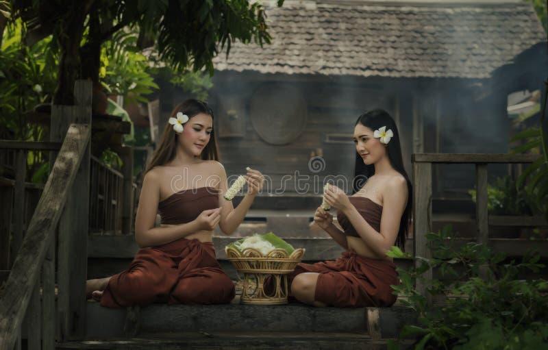 Mujeres de Tailandia en el vestido tradicional que se sienta para hecho de las guirnaldas de la flor imagen de archivo libre de regalías