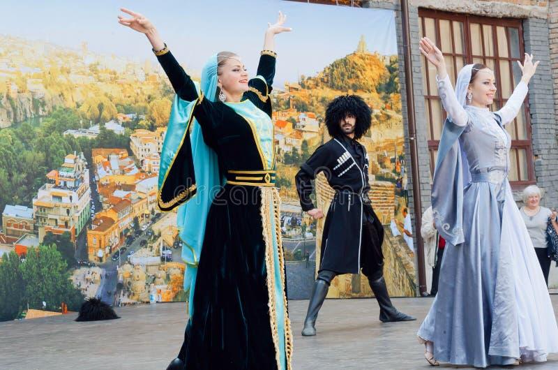Mujeres del baile del grupo étnico de los bailarines del país de Georgia que hace la demostración al aire libre foto de archivo libre de regalías