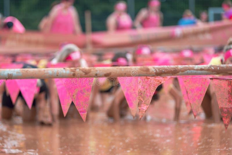 Mujeres del corredor de raza del fango que se arrastran en el fango bajo obstáculos imágenes de archivo libres de regalías
