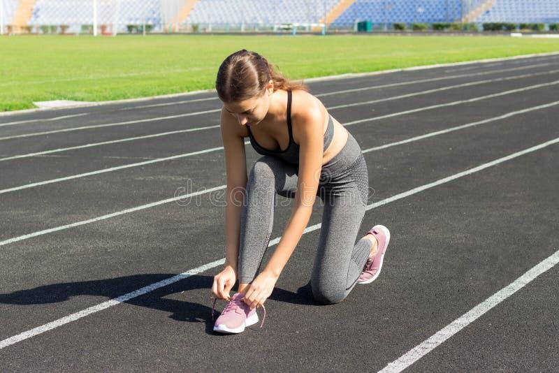Mujeres del corredor que atan los cordones de zapatos que consiguen listos para la raza en pista corrida en deporte del estadio y imagen de archivo