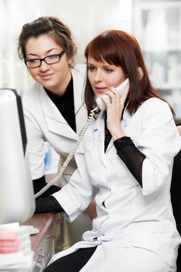 Mujeres del químico de la farmacia en droguería con el teléfono fotos de archivo libres de regalías