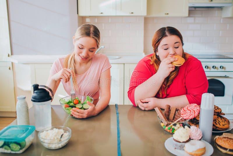 Mujeres delgadas y gordas hambrientas jovenes en cocina que comen la comida Comida sana y malsana Ensalada contra la hamburguesa  foto de archivo libre de regalías
