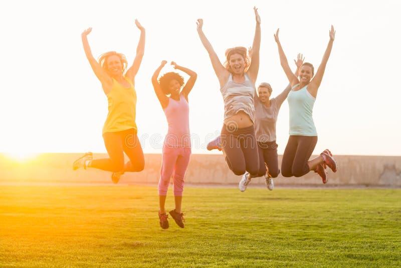 Mujeres deportivas felices que saltan durante clase de la aptitud fotografía de archivo libre de regalías