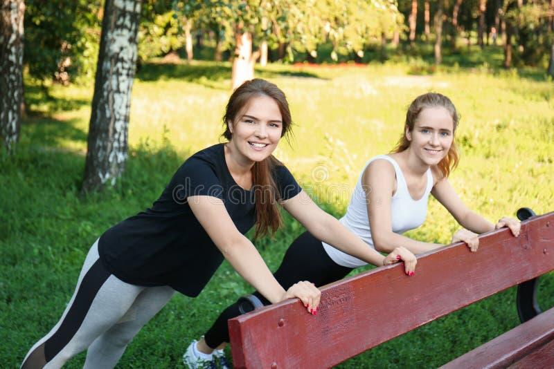 Mujeres deportivas jovenes que hacen ejercicios en banco al aire libre imagen de archivo libre de regalías