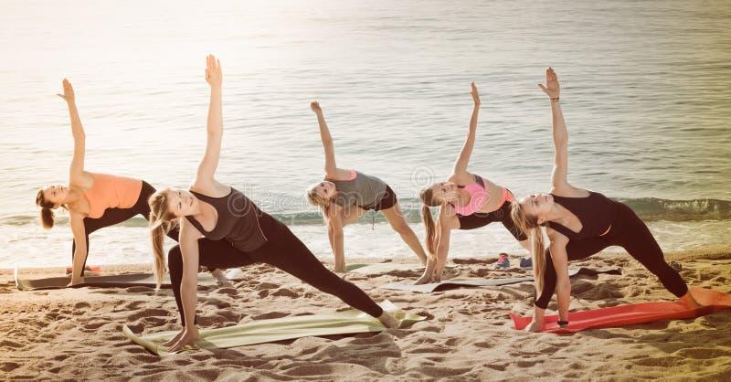 Mujeres deportivas jovenes que practican posiciones de la yoga foto de archivo
