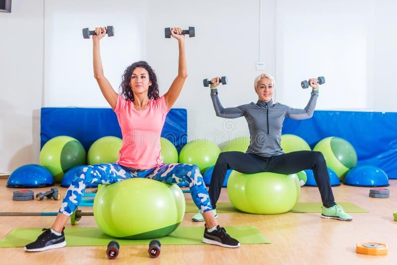 Mujeres deportivas que entrenan dentro a hacer el ejercicio que se sienta en las bolas de la aptitud que levantan pesas de gimnas imagen de archivo libre de regalías