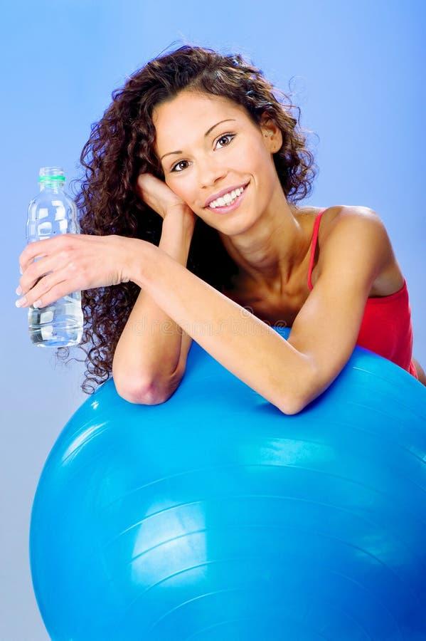 Mujeres detrás de la bola azul de los pilates que sostiene la botella de agua foto de archivo libre de regalías