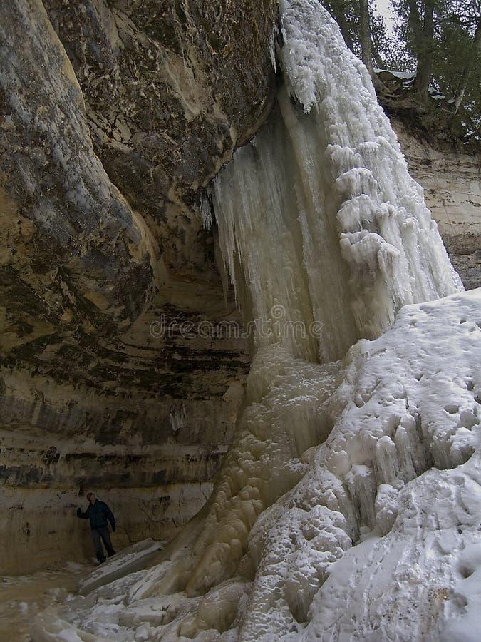 Mujeres detrás de la cascada congelada fotos de archivo libres de regalías