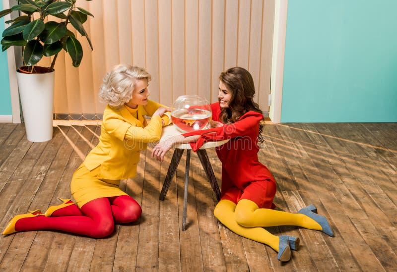 mujeres diseñadas retras sonrientes que se sientan en piso cerca de pescados de oro en acuario en la muñeca de la mesa de centro foto de archivo
