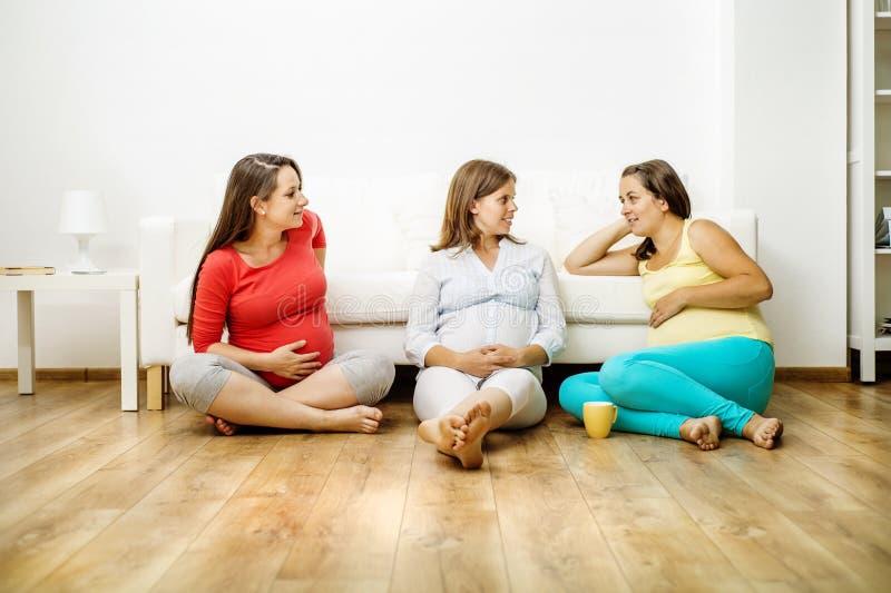 Mujeres embarazadas en el sofá imagenes de archivo