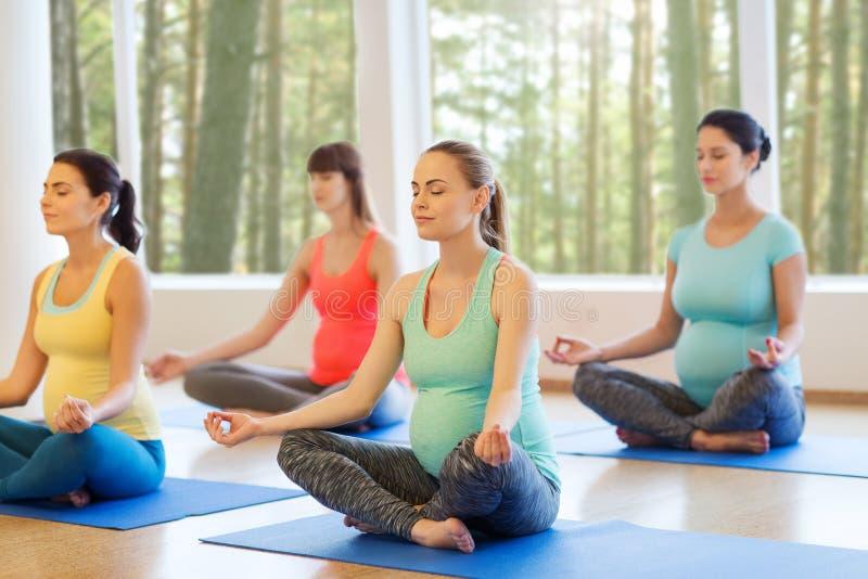 Mujeres embarazadas felices que ejercitan yoga en gimnasio foto de archivo