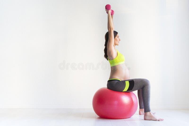 Mujeres embarazadas jovenes una que hacen ejercicios de la aptitud fotos de archivo libres de regalías
