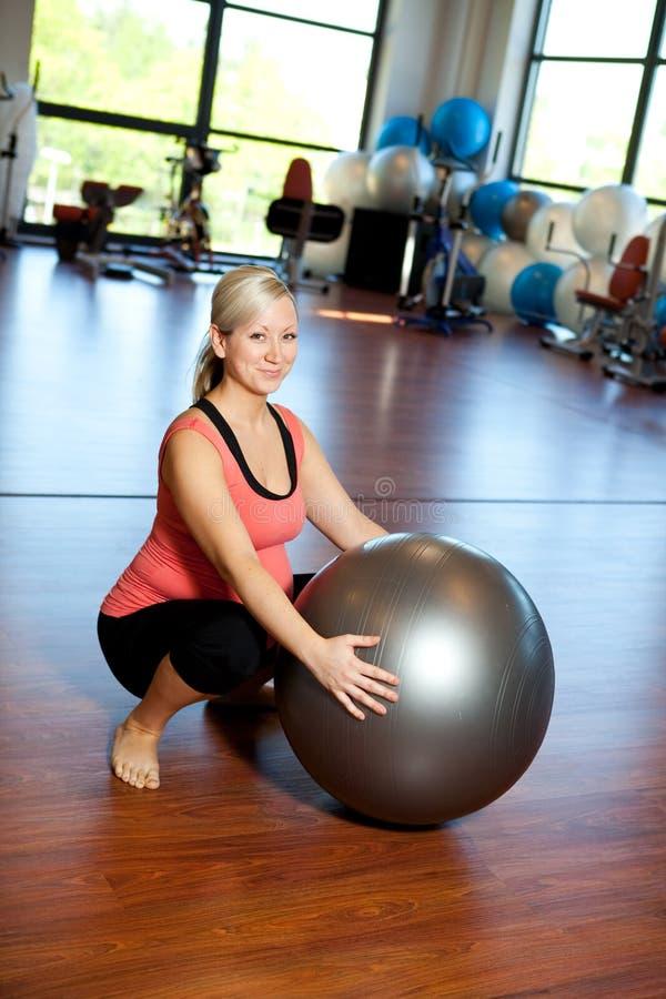 Mujeres embarazadas que hacen ejercicio el ponerse en cuclillas. imagen de archivo libre de regalías