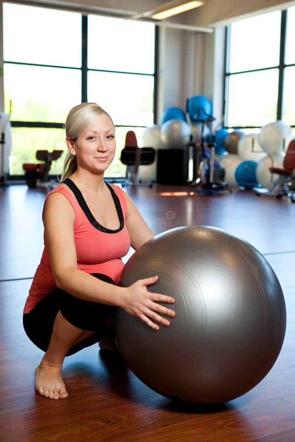 Mujeres embarazadas que hacen ejercicio el ponerse en cuclillas. fotos de archivo libres de regalías