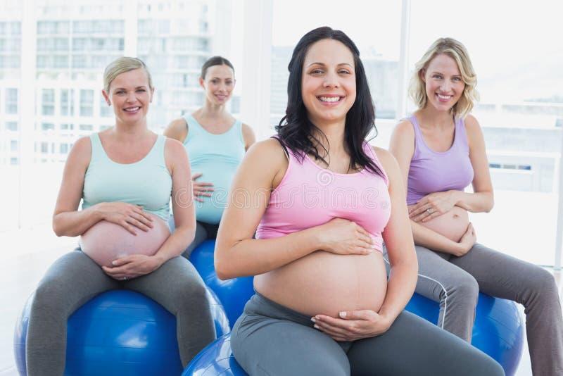 Mujeres embarazadas sonrientes que se sientan en bolas del ejercicio fotos de archivo
