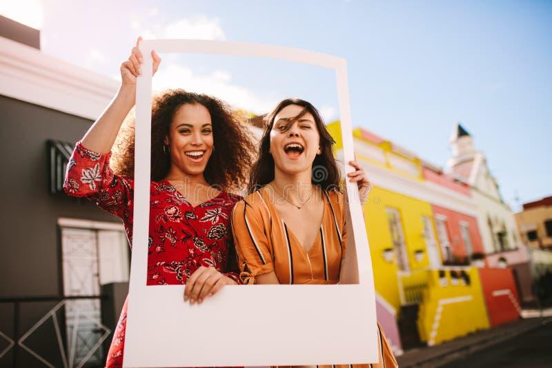 Mujeres emocionadas al aire libre con un marco de la foto foto de archivo libre de regalías