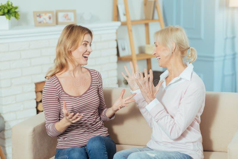 Mujeres emocionales que comparten grandes noticias y que parecen excitadas fotografía de archivo