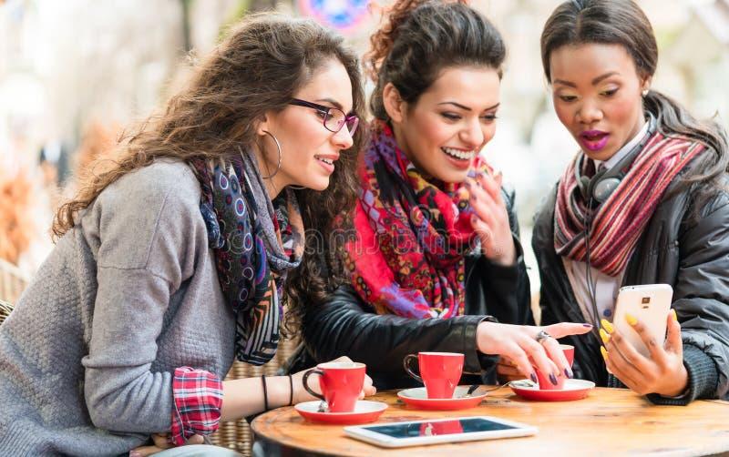Mujeres en el café que muestra imágenes en el teléfono elegante imagen de archivo